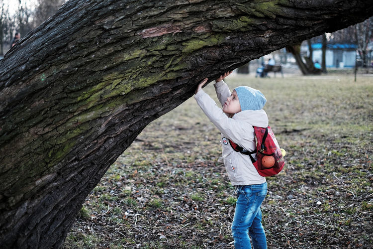 Side view of boy touching tree trunk at park
