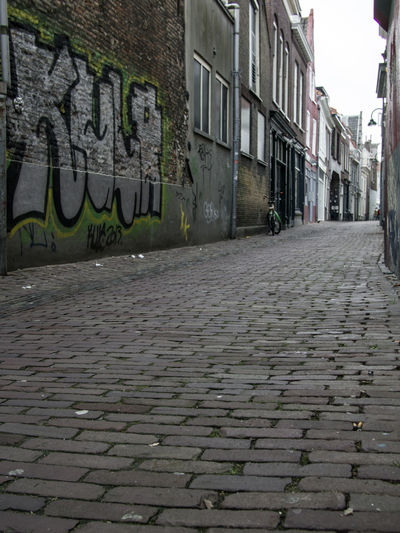 Building Exterior Built Structure Architecture City Street Graffiti Text Footpath Day Communication Wall - Building Feature Building Art And Craft Cobblestone Western Script Direction The Way Forward No People Creativity Sidewalk Outdoors Paving Stone Alley