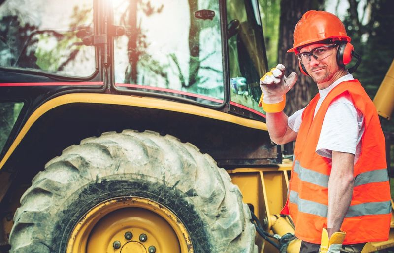Portrait of manual worker standing by earthmover