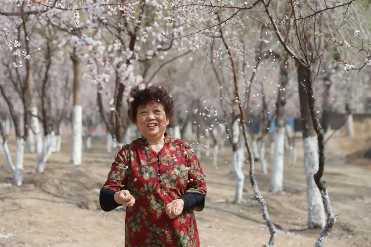 Senior Woman Standing At Park During Springtime