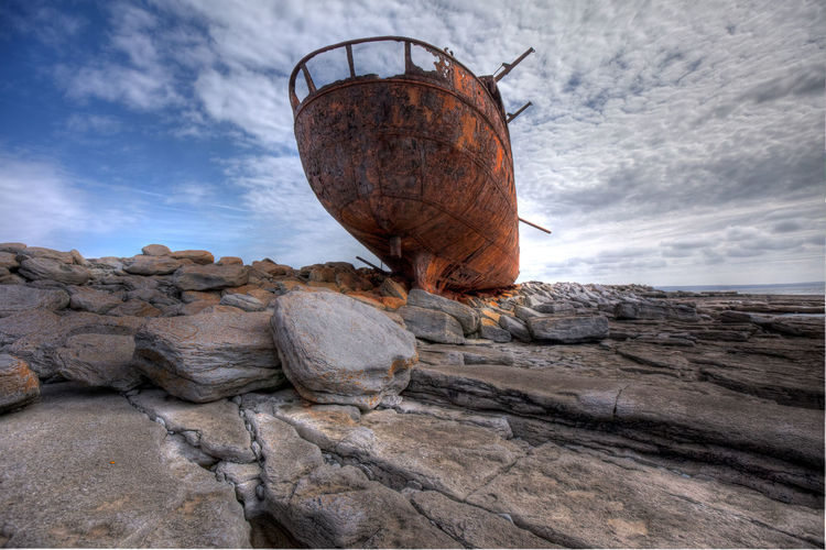 Shipwreck on rocky sea shore against sky