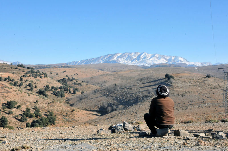 Rear view of man sitting on land against clear sky