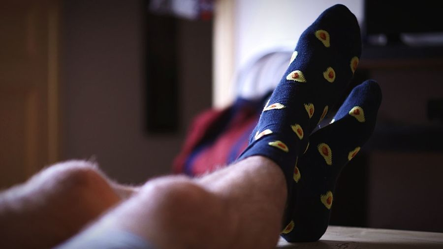 Low section of man wearing socks with feet up on table at home