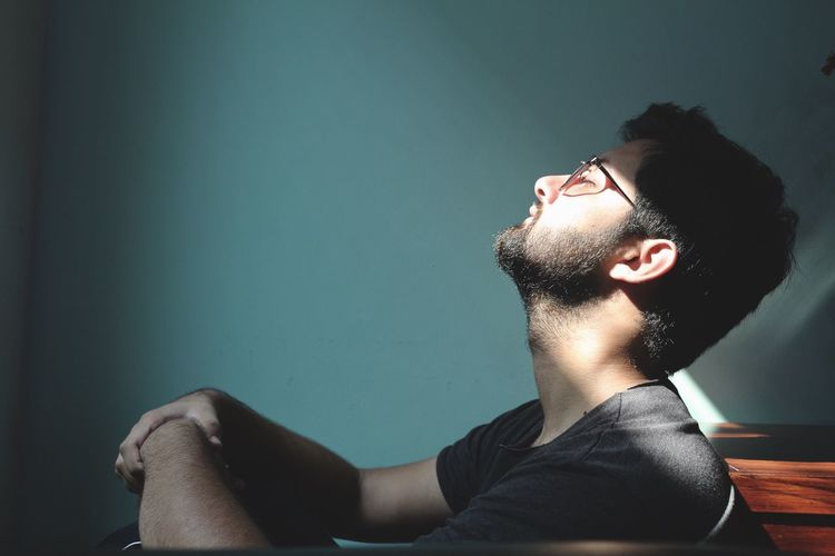 Side View Of Man Sitting Against Blue Wall