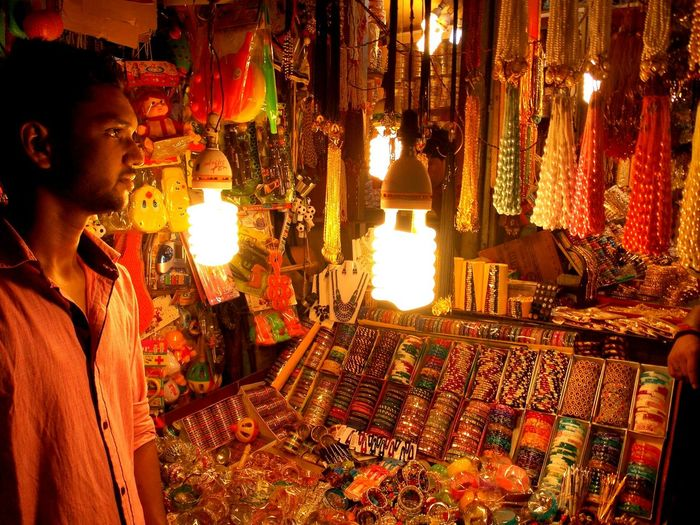 Bangle seller standing by illuminated market stall at night