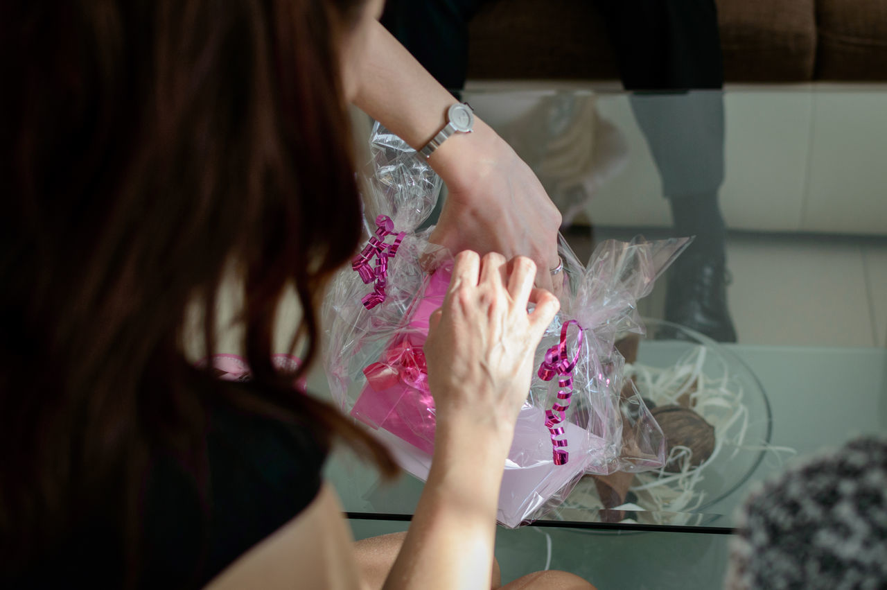 Cropped Woman Removing Gift Box At Glass Table