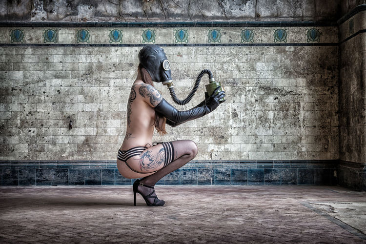 Full length of sensuous naked woman wearing gas mask against wall