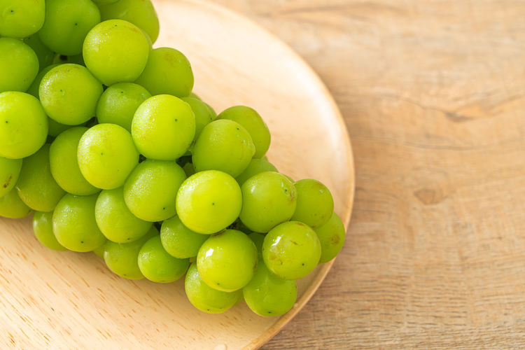High angle view of grapes in bowl on table