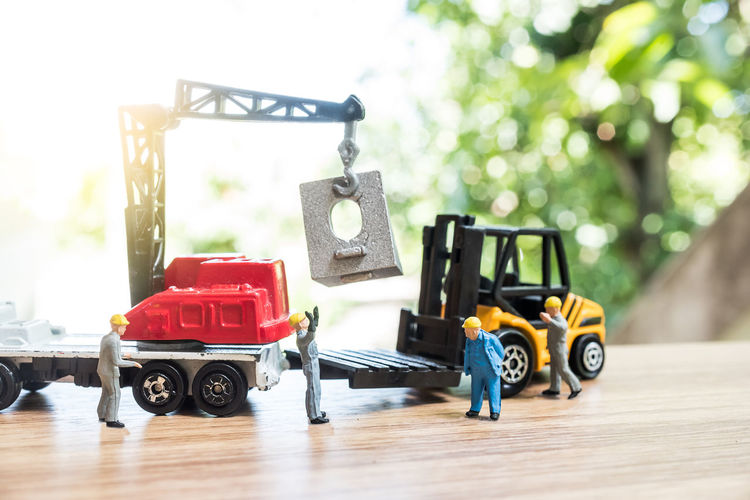 Close-up of figurines with toy crane and forklift on table