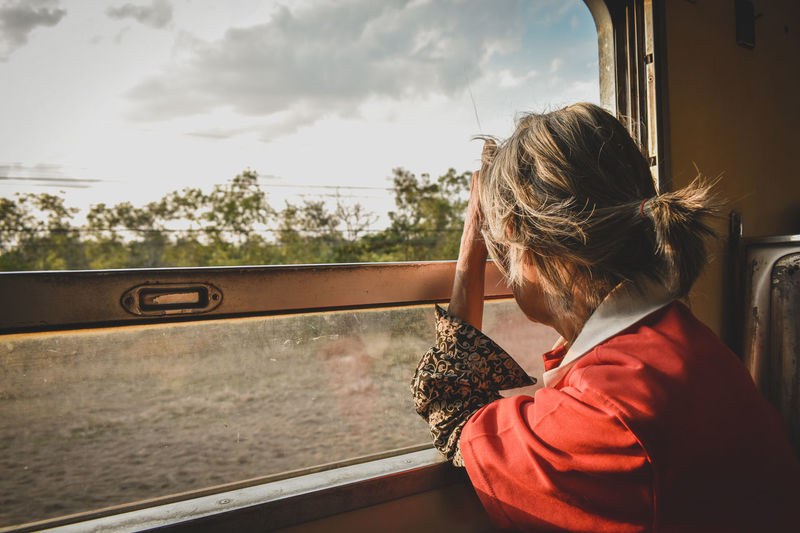 Senior Woman Looking Through Train Window Against Sky