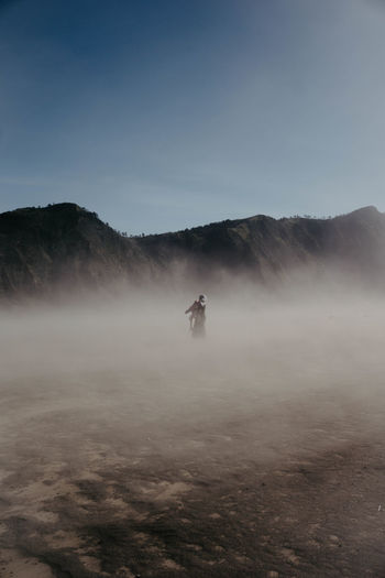 Man on mammal against mountains and sky