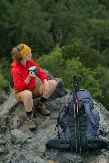 caucasian hiker standing on a rocky peak Alpine Backpacking Camping Expedition Freedom Hiking Nature Rock Travel Trekking Woman Activity Adventure Backpack Caucasian Climbing Day Female Full Length Hiking Holding Holiday Land Leisure Activity Lifestyles Mountain Nature Outdoors Outside Peak People person Plant Real People Sitting Tree Trip Vacations Walking
