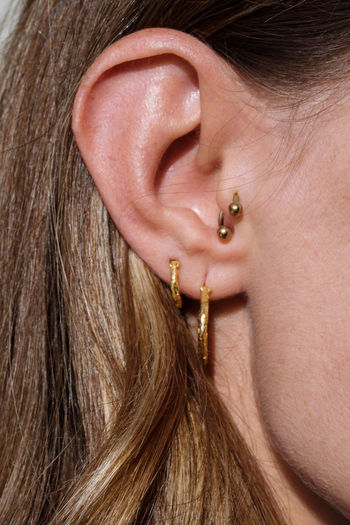 Close up of a woman ear with multiple earrings