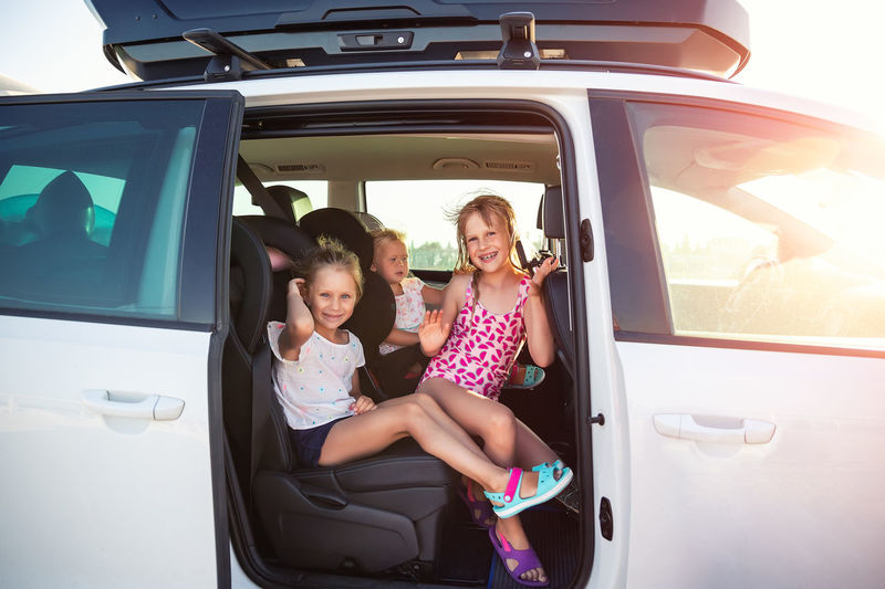 Portrait of happy girl sitting in car