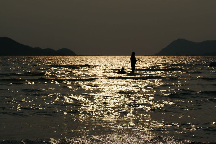 Silhouette person on sea against clear sky