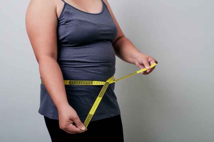 Midsection of woman measuring waist against gray background