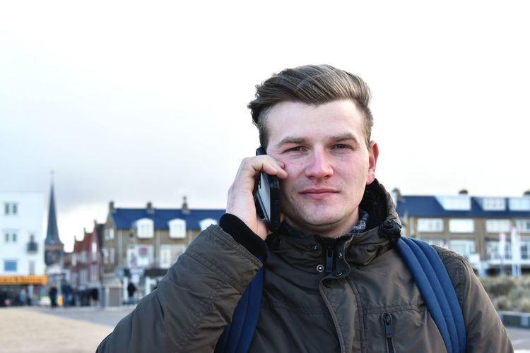 Portrait of man talking on mobile phone against sky
