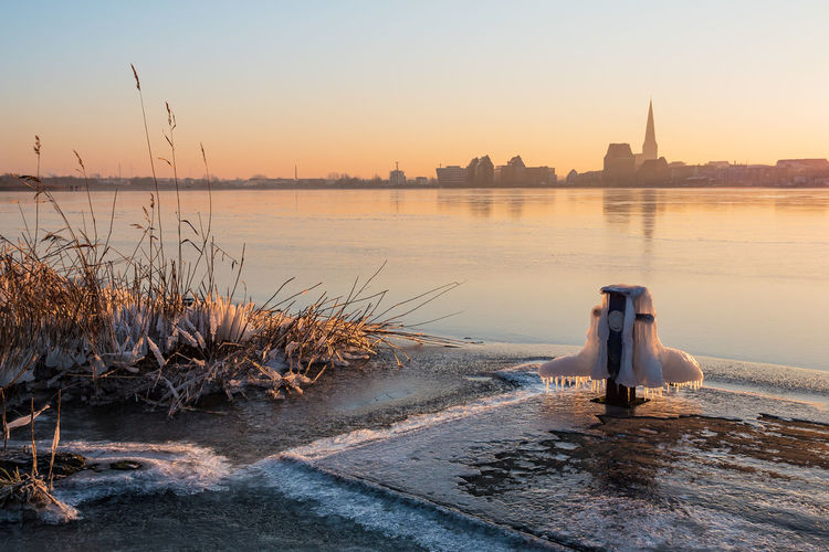View over the river Warnow to Rostock, Germany. Frozen Holiday Ice Morning Rostock Winter Architecture Bollard Building Exterior City Day Nature No People Outdoors River Sky Snow Sunrise Sunup Tourism Town Travel Destinations Vacation Warnow Water
