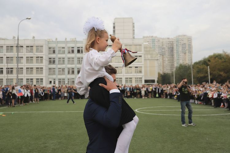 Side view of young man carrying girl on shoulders while standing on sports field