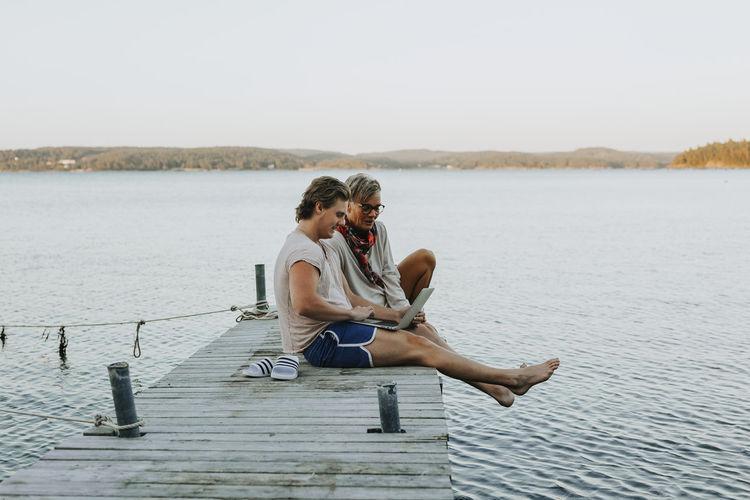 Young couple sitting on lake