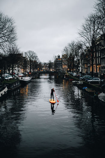 Man on boat in river against sky