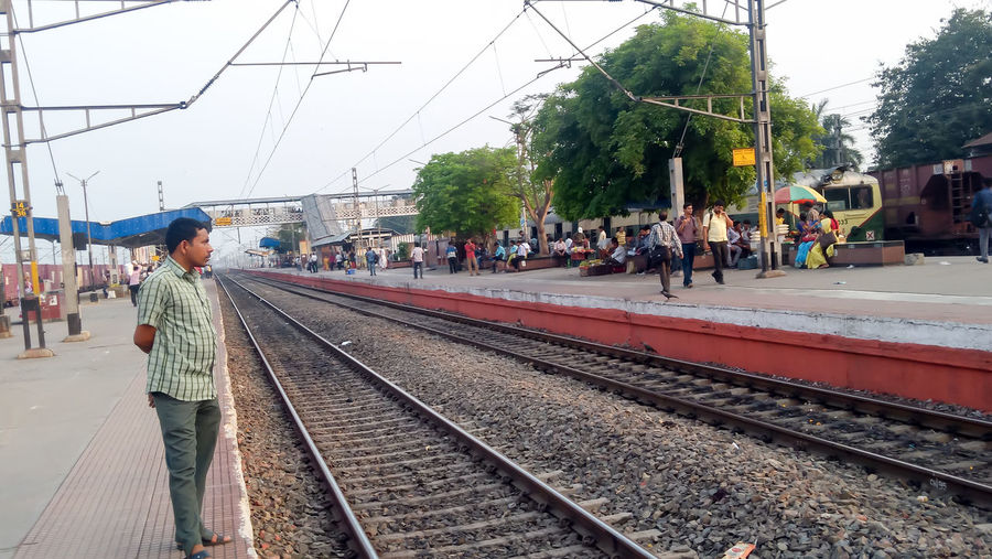 People waiting at railroad station against sky