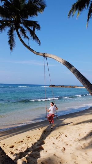 Woman swinging on rope swing at beach against sky