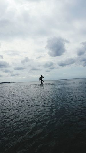 Scenic View Of Man Surfing In The Sea Against Cloudy Sky