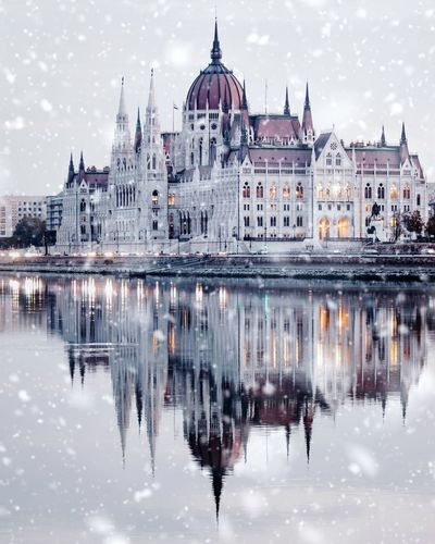 Reflection Of Buildings In River During Snowfall