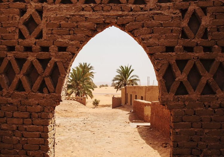 Building By Palm Trees Seen From Archway In Brick Wall