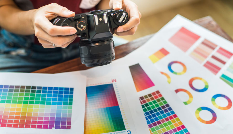 Midsection of design professional holding camera over color swatches at office