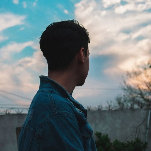 Side view of thoughtful young man looking away against sky during sunset