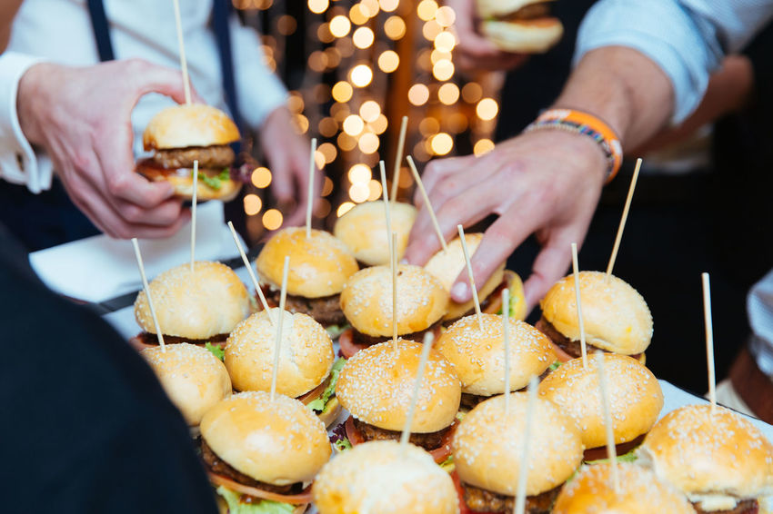 Burger Celebration Close-up Drink Focus On Foreground Food Food And Drink Freshness Hamburger Hand Holding Human Body Part Human Hand Lifestyles Men Midsection Outdoors People Real People Tray Two People