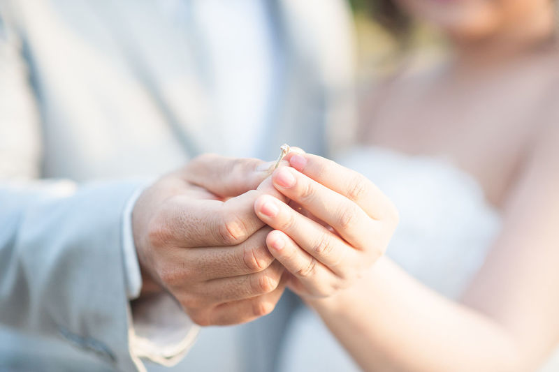 Midsection man putting ring to bride during wedding ceremony
