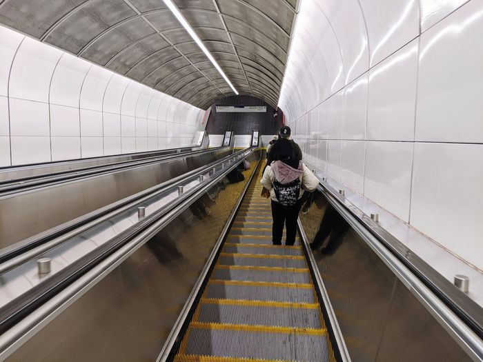 Rear view of woman on escalator at railroad station