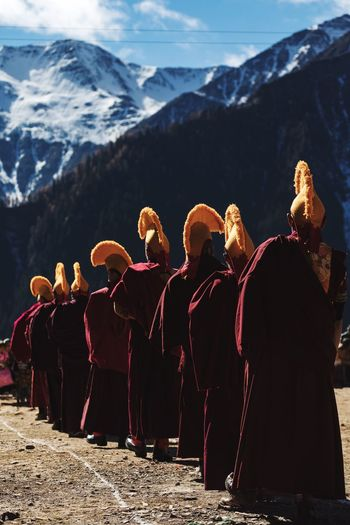 Rear view of monks standing by snowcapped mountain