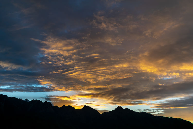 Low angle view of silhouette mountain against dramatic sky