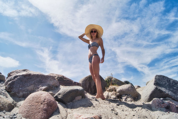 Full length of young woman in bikini standing on rock against sky