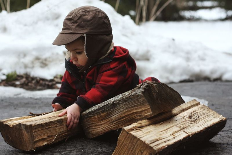 Close-up of boy holding firewood on road during winter