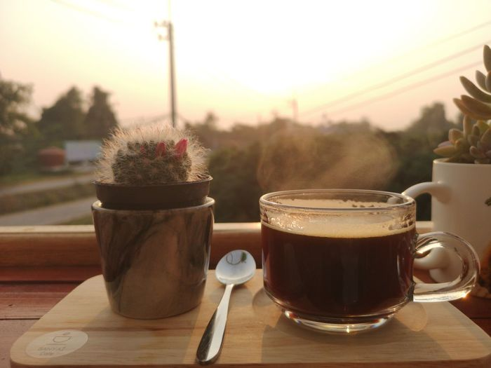 Close-up of coffee served on table against sky during sunset