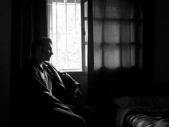 Side view of woman sitting in window