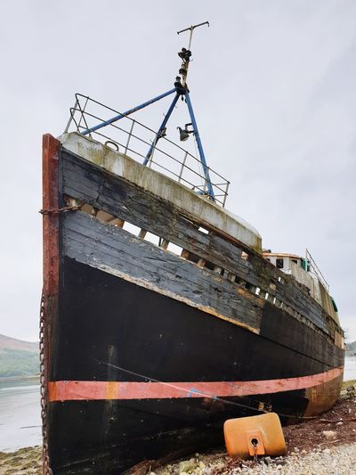 Abandoned ship moored in water against sky
