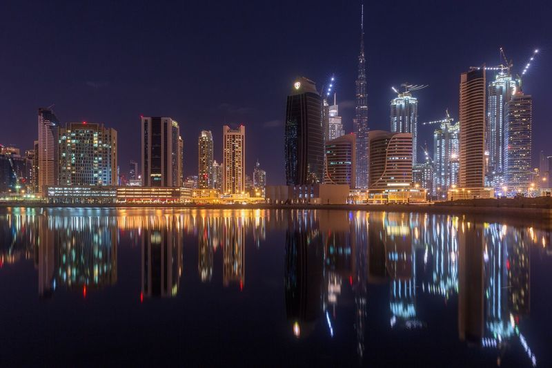 Illuminated cityscape reflecting in sea against sky at night