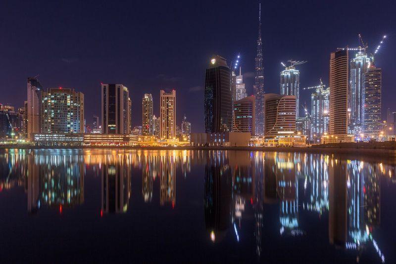Illuminated cityscape reflecting in sea against sky at night