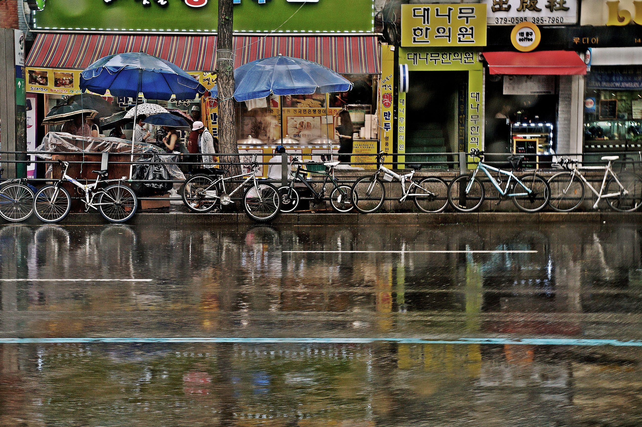 water, bicycle, rainy season, reflection, wet, protection, day, transportation, outdoors, land vehicle, text, no people, architecture