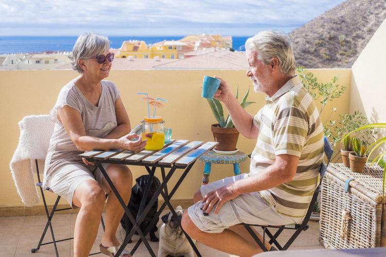 Senior couple with dogs sitting on balcony