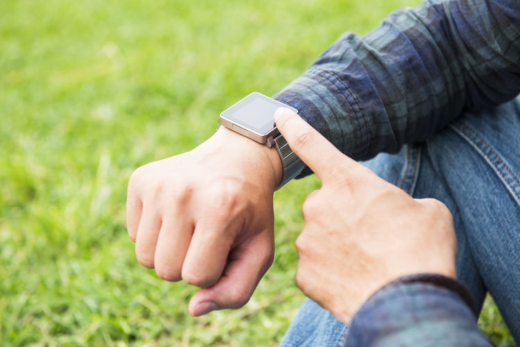 Midsection Of Man Touching Wristwatch