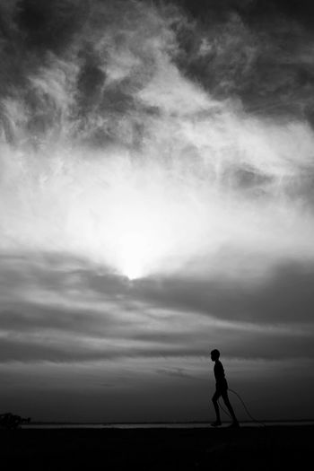 Silhouette man standing on land against sky