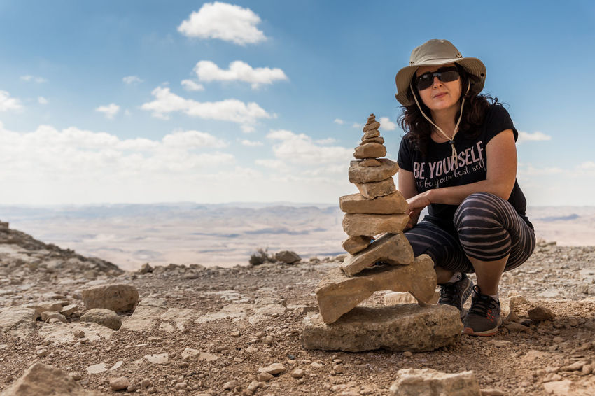 A young woman sits leaning on her knee near several stones stacked one on top of the other in the Judean Desert in Israel Happy Sitting Woman Background Balance Beautiful Woman Cloud - Sky Fashion Hand Harmony Hat Healthy Lifestyle Israel Judean Desert Knee Land Leisure Activity Lifestyles Nature Relaxation Rock Sky Stacked Stones Young Adult Young Woman