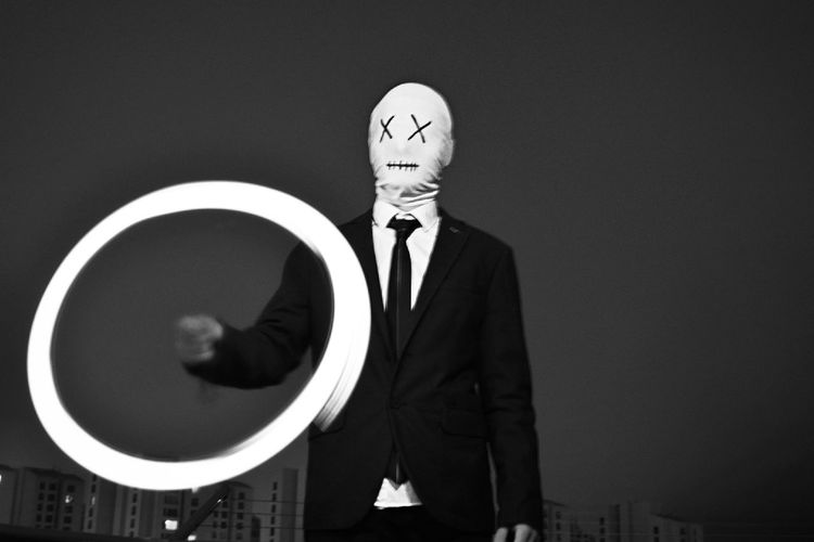 Businessman Wearing Mask Making Light Painting Against Clear Sky At Night